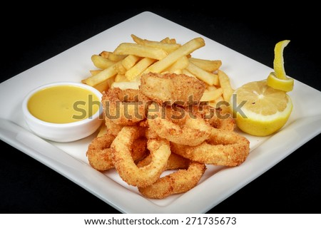 Calamari rings :An delicious dish of deep fried calamari and french fries Location: At Rawan Cake in Amman ,Jordan - stock photo