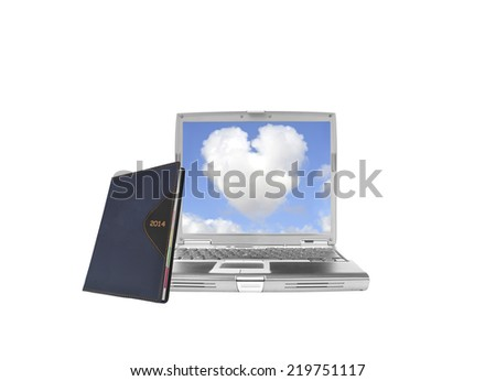 2014 Calendar Datebook leaning on laptop with heart shaped cloud blue sky isolated on white background - stock photo