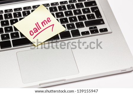 """call me"" written on sticky note, on laptop keyboard. - stock photo"