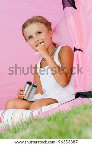Camping in tent - lovely girl on summer vacation - stock photo