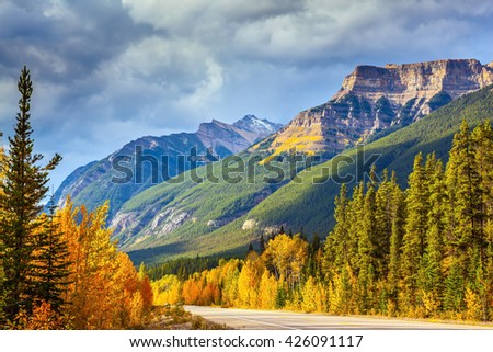 Canada, Alberta, Rocky Mountains. Highway in Banff National Park. Mountains and colorful autumn forest illuminated by the sunset - stock photo