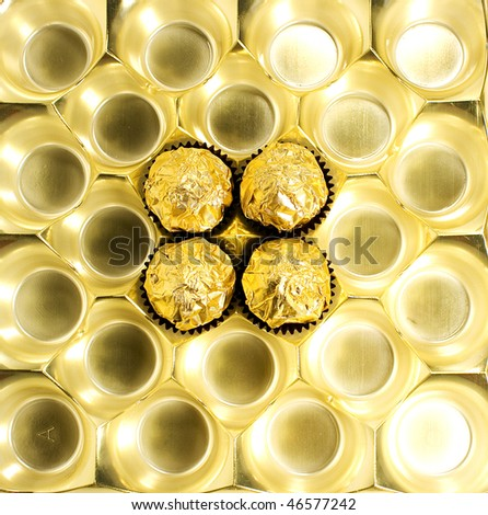 4 candies wrapped in golden foil in the candy box - stock photo