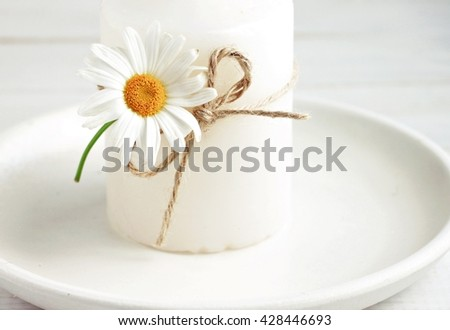 Candle decor simple summertime style. Candlestick decorated fresh daisy flower. Soft light and focus.  - stock photo