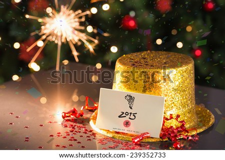 2015 card on table set for party with gold hat and sparkler - stock photo