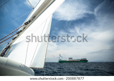 Cargo ship on the high seas, in the foreground sail yacht. Picture with space for text. - stock photo