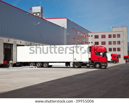 cargo trucks at an entrance of a warehouse - stock photo