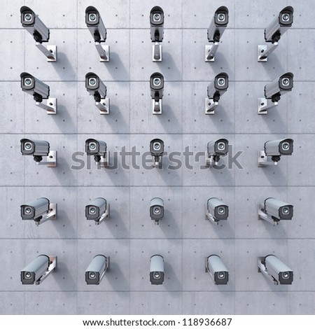 25 cctv camera watching you on concrete wall - stock photo