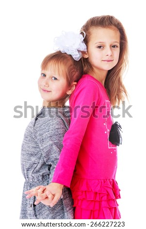 Charming sister huddled back to back.- isolated on white background - stock photo