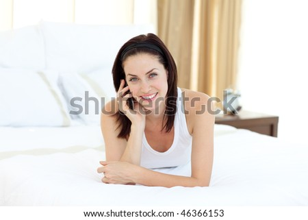 Charming woman talking on phone lying on her bed - stock photo