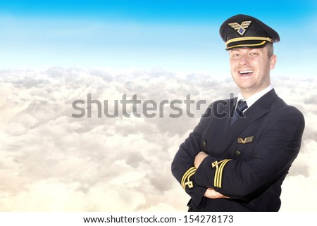 Cheerful pilot on a background of clouds - stock photo