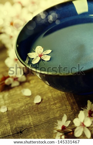 cherry blossom flowers with bowl of water on wooden background - stock photo