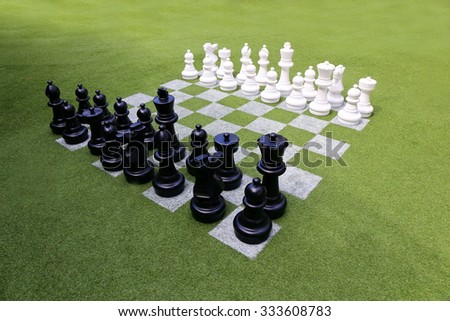 Chessboard and chess pieces on the grass in the garden,playing wooden chess pieces, business teamwork competition games concept, leadership hand of businessman playing chess. - stock photo