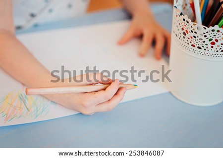 child girl drawing with pencils at home on blue wooden table - stock photo