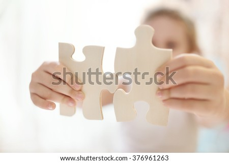 Child girl holding  two big wooden puzzle pieces. Hands connecting jigsaw puzzle. Close up photo with small dof. Education and learning concept. - stock photo