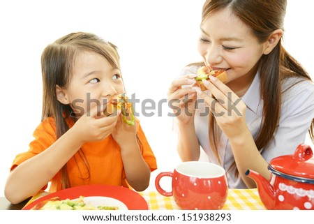 Child with mother eating foods - stock photo