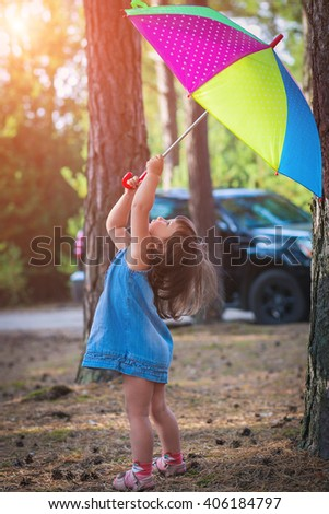 childhood, leisure, friendship and people concept.  Little girl in denim dress playing in a pine forest with color umbrella.  soft light effect. Sunny summer day. Happy family. jaunt - stock photo
