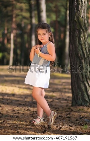 .childhood, leisure, friendship and people concept. Small girl in a pine forest with cones in her hands.  Sunny summer day. Happy family. jaunt - stock photo