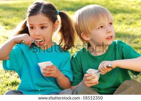 Children about yoghurt. In park. Emotions - stock photo