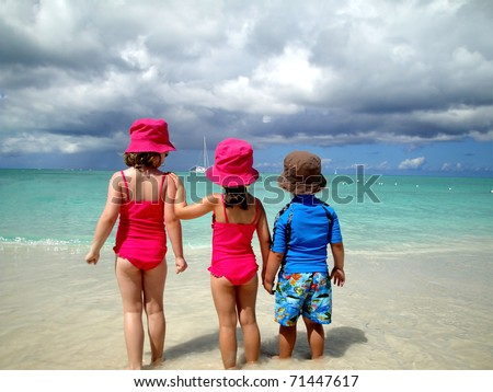 children on the beach looking at ocean - stock photo