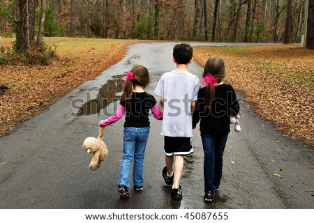 3 children playing outdoors walking on the road - stock photo
