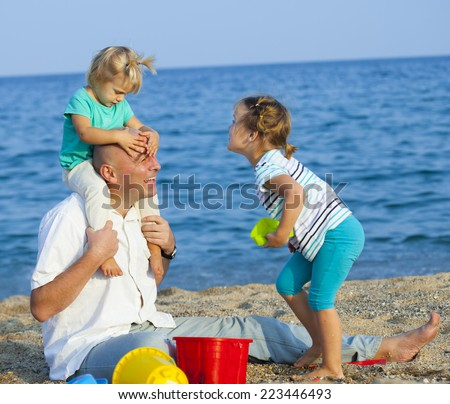 Children with Dad on  beach  at summer day. - stock photo