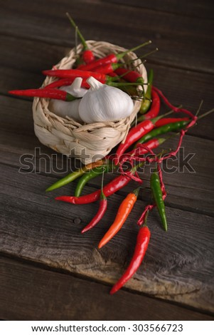 chili peppers and garlic on old wooden table - stock photo