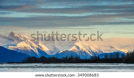 Chilkat River and Mountains in snow on a sunrise. Alaska.USA - stock photo