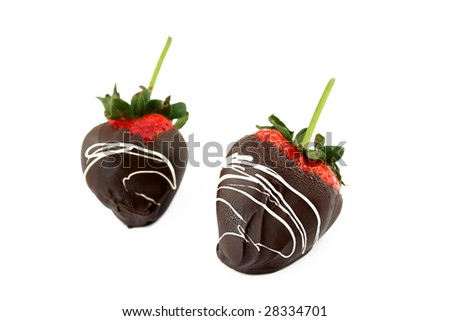 chocolate covered strawberries on a white background with another strawberry out of focus in the back. Used a shallow depth of field and selective focus. - stock photo