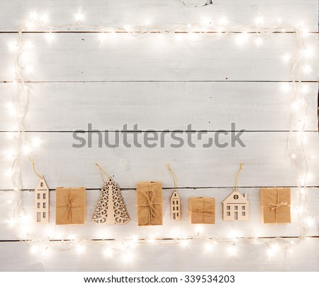 christmas decoration on wooden table -  houses, tree, xmas lights and copy space for text - stock photo