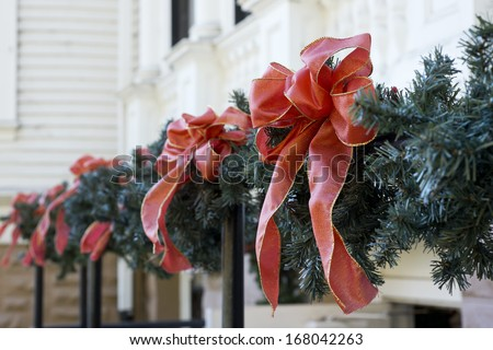 Christmas decorations, red ribbons and fake pine branches place on outdoor railing, shallow focus - stock photo