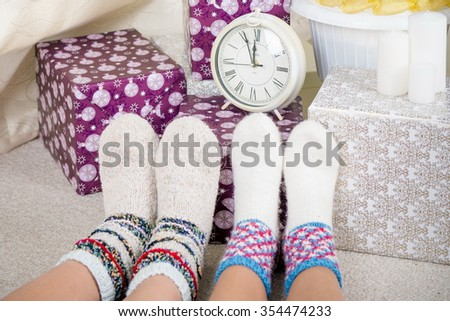 Christmas Eve! Five minutes before the new year. two pairs of feet in knit socks and hours under the tree. waiting for Christmas. - stock photo