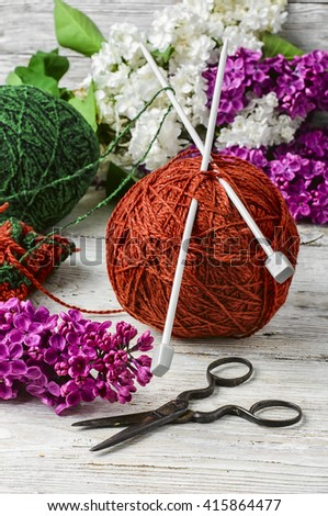 clew of wool yarn for knitting and branches of lilac blossoms - stock photo