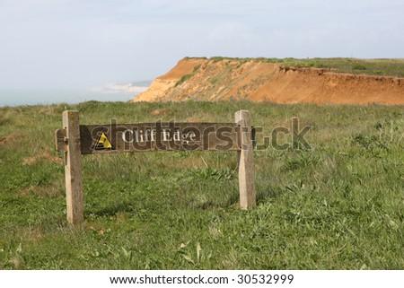 'Cliff Edge' Warning sign near edge of high cliffs - stock photo