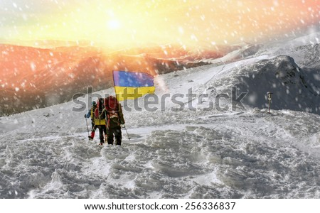 Climbing the Christmas Ukrainian climbers on the top of the main country - Goverla on the Montenegrin ridge, with the state and the flag and the Rebel Army Roman Shukhevych and Stepan Bandera - stock photo