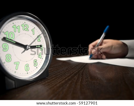 clock with a man doing written test in the background, low key, useful for job application.education and other testing related themes - stock photo