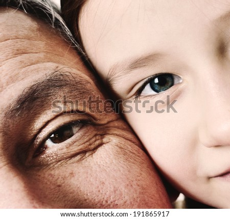 Close up detail of a little girl and her grandfather with their faces pressed close together. Young and Old. - stock photo