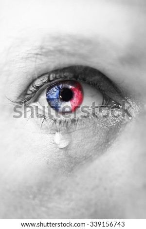 Close up eye of young man crying sad in tears with french flag reflection on his iris, black and white isolated color edition - stock photo