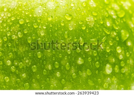 close-up from a green apple with drops of water as a background texture - stock photo
