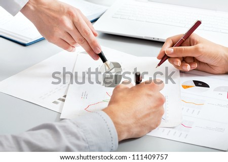 Close-up of hands of business people at work in the office - stock photo