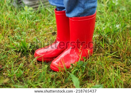 Close up of kid feet walking in red boots in green grass - stock photo