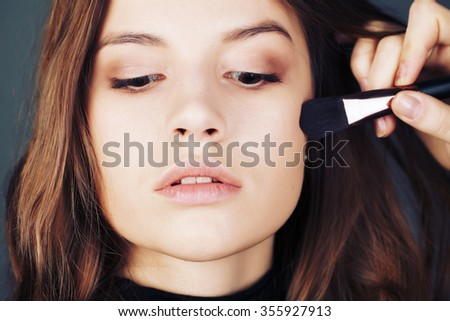 Close-up portrait . In the face of the girl model, make-up artist on the basis of tone is a special brush. Face Care , bb and cc cream. Nude make up - stock photo