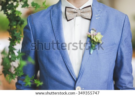close-up portrait of stylish groom in a blue suit with a tie and a flower buttonhole butterfly on the lapel on the wedding day - stock photo