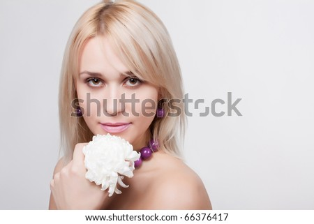 close up Portrait of the young  beautiful woman with a flower on a light background - stock photo