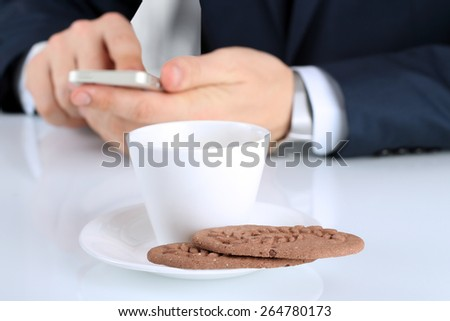 closeup image of Cup of coffee with cookies .Businessman holding  and using the  mobile  smart  phone on a background - stock photo