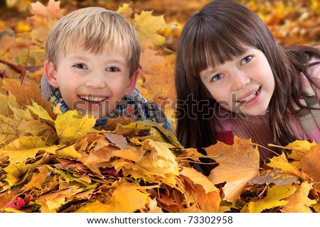 Closeup of smiling young sister and brother playing in colorful Autumn leaves with wood in background. - stock photo