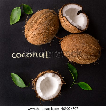 """Coconut"" poster. Coconut with green leaves isolated on a black background. Broken coconut. - stock photo"