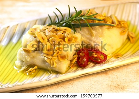 Cod fish with garlic chips. Portuguese and Brazilian traditional food. - stock photo