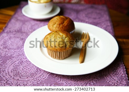 coffee and banana muffins in paper cupcake  with nuts on white plate,Dessert cakes with banana and coffee at table selective focus - stock photo