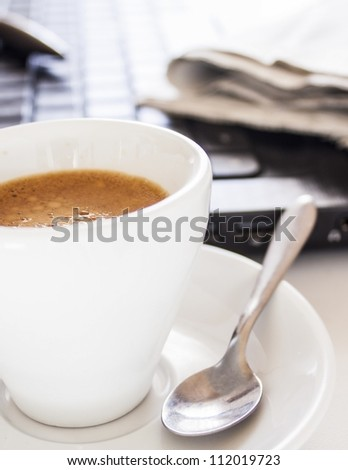 coffee cup with newspaper and laptop - stock photo
