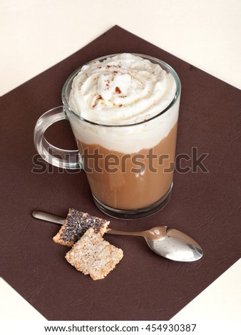 Coffee in glass cup with whipped cream and  cookie. - stock photo